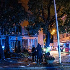 Personer står utanför Kåren i Åbo. I bakgrunden en brandbil.