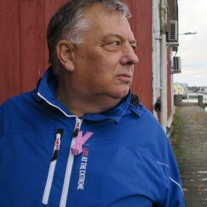 En man med grått hår och blå jacka (Mats Lagerstam) står på en brygga vid båthamnen i Ekenäs. Stallörsparken. Bakom ser man lite av ett rött trähus.