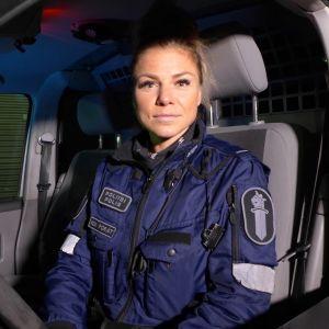 naisylikonstaapeli istuu poliisiautossa