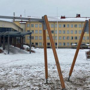 Nelikerroksinen koulurakennus jonka talvinen piha on tyhja-
