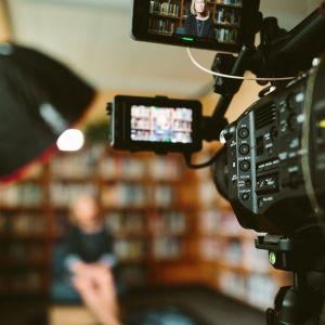 En tv-intervju pågår, en kvinna intervjuas i ett bibliotek, filmkameran är i fokus och en lampa som lyser mot kvinnan syns också i förgrunden.
