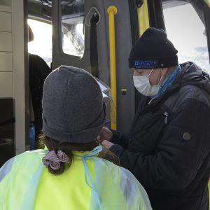 En äldre man vid en ambulans skriver på ett papper