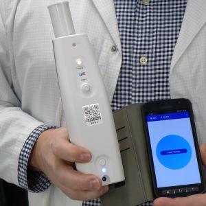 En person håller i en blåstestapparat och en mobiltelefon.
