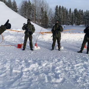 En instruktör visar fyra män i uniform med vapen i hand.