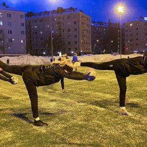 HJK:n 06 akatemiajoukkueen nuoret lämmittelevät pimenevässä illassa Töölön pallokentällä.