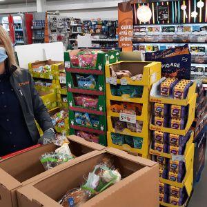 kauppias kerää laatikkoon ruokaa