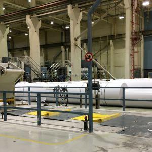 Industrihall med stora vita pappersrullar och en maskin till vänster. Finpappersmasking vid bruket i Uleåborg stängdes hösten 2020.