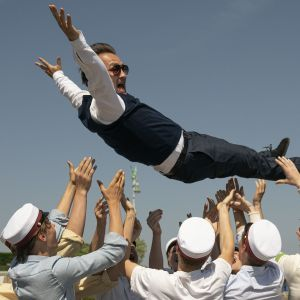En av huvudpersonerna i filmen Druk kastas upp mot himlen av ett gäng glada studenter.