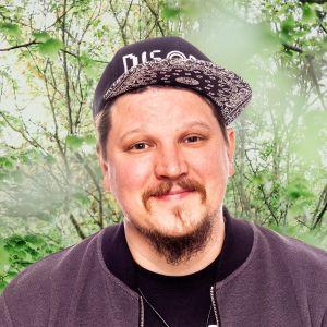 Benjamin Särkkä småler rakt in i kameran. Bakgrunden är en grönskande skogsdunge.