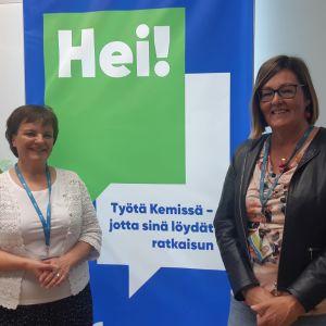 Kaksi naista työllisyyspalveluita mainostavan taulun edessä.