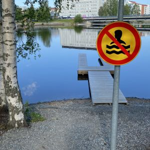 Kuvassa Limppusaaren uintikieltomerkki, jonka taustalla laituri vedessä. Horisontissa näkyy Kajaanin keskustaa.
