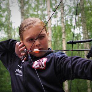Nuori tyttö ampuu jousella