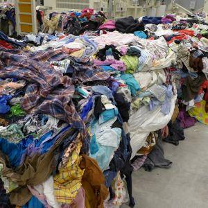 Kierrätystä odottavia vaatteita kasassa.
