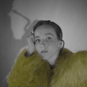 Lavarunoilija Elsa Tölli nojaa käteensä ja katsoo suoraan kameraan. Hänellä on yllään keltainen turkki, ja hänen takanaan olevalla kankaalla on saksofonisti Linda Fredrikssonin varjo.