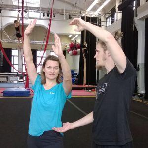 Sirkustaiteilija Jori Reunanen opettaa Pirjo Koskiselle yhden käden kärrynpyörää