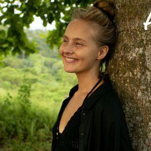 Kuvassa Away-Tiiu hymyilee kauniissa ympäristössä luonnossa.