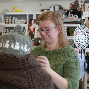 Sara Blomqvist tittar till en skyltdocka i sin garnaffär