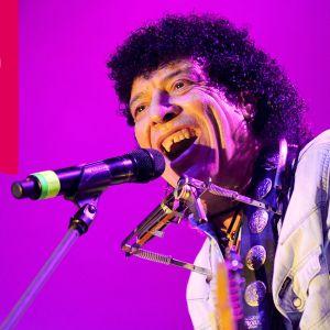 Ray Dorset från Mungo Jerry har ett munspel i en ställning kring halsen och sjunger i en mikrofon.
