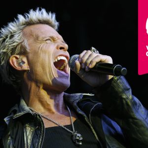 Billy Idol sjunger i en mikrofon som han håller i handen.