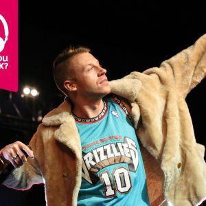 Rapparen Macklemore sträcker upp ena armen med en mikrofon i andra handen.