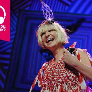 Artisten Sia ler brett med öppen mun.
