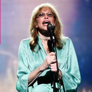 Carly Simon sjunger i en mikrofon som är i en mikrofonställning.