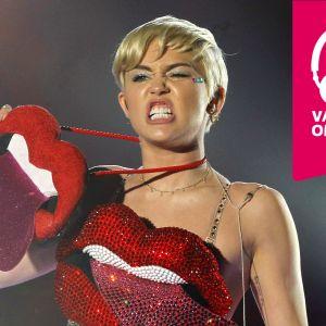 Miley Cyrus grimaserar och håller upp en stor konstgjord mun som har tungan utsträckt.