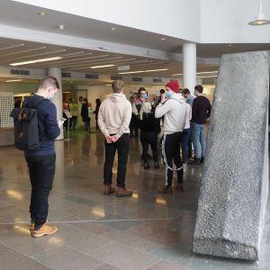 Opiskelijat ruokajonossa yliopiston aulassa maaliskuussa 2021.