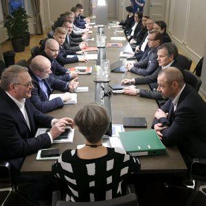 Människor sitter samlade runt ett långt mötesbord.