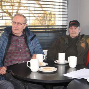 tre män på café