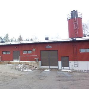 En lång låg röd byggnad.En bil står parkerad utanför. Grått vinterväder, lite snö.