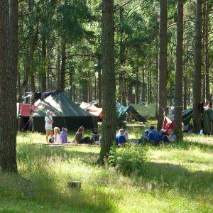 Tält och ungdomar på scoutläger i Syndalen sommaren 2009.
