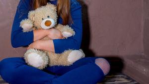 Ett barn med en teddybjörn i famnen.