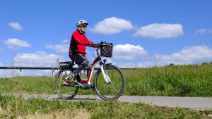 En kvinna åker på en elcykel. I bakgrunden syns blå himmel och grönt gräs.