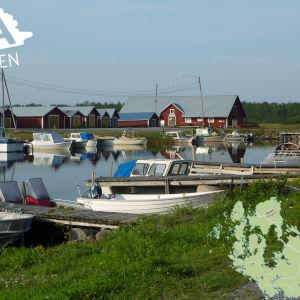 Båtar i Björköby hamn. En karta med närmaste bankautomat i hörnet av bilden.