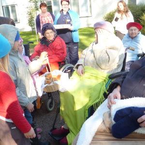 Barn från Solgårdens daghem bjuder bullar åt invånarna i Villa Pentby då Alfa Omega Raseborg ordnar rollatorrally.
