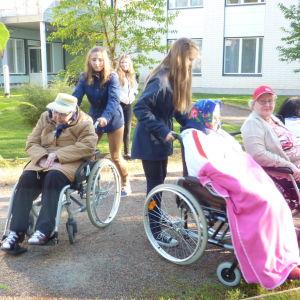Tinja Rolin och Lisa Nyholm i årskurs 8 i Karis svenska högstadium hjälper invånarna tillrätta inför Alfa Omega Raseborgs rollatorrally 2014.