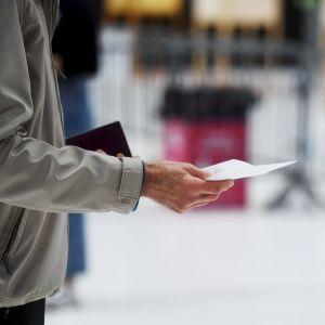 En person har fått en röstsedel och instrueras av en valfunktionär