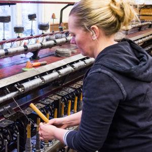 Alicia Trezise-Segervall trär upp garn i en spinnmaskin.