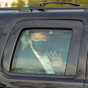 Donald Trump vinkar från fönstret på en svart bil.