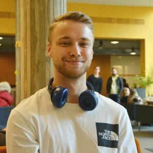 en kille i vit skjorta med hörlurar runt halsen, i bakgrunden syns andra studenter