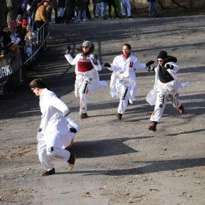 Fyra vitklädda personer springer ner för backen i full fart.