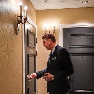 En man i kostym öppnar dörren till ett hotellrum.