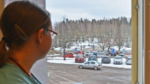 Kvinna i sjukskötardräkt tittar ut genom ett fönster mot en parkeringsplats.
