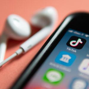 En telefon och ett par hörlurar ligger på ett persikofärgat bord. På telefonen syns olika appar, bland annat Tiktok och Instagram.