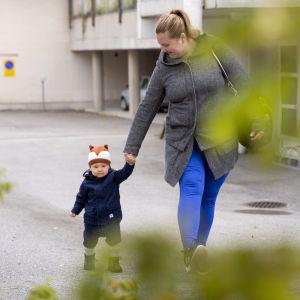 En kvinna går på en parkering och håller sin ettåriga son i handen.