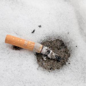 En brinnande cigarrettfimp som slängts i snön.