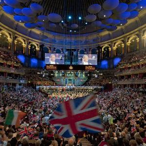 Valtava yleisöjoukko Royal Albert Hallin salissa. Etualalla suuri Britannian lippu.