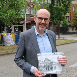 Borgmästaren Koen Palinckx visar platsen där Leopoldstatyn stod förut. I handen har han en svartvit bild över statyn.