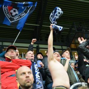 Supportrar på läktaren under en fotbollsmatch. En man har tagit av sig sin skjorta och svänger med en blåsvart halsduk. De andra har jackor och mössor på sig.